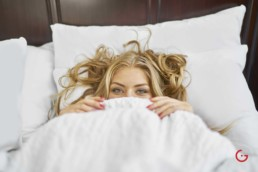 Girl Playful Eyes in White Bed - Photographer Lifestyle Photography Wardrobe Stylist