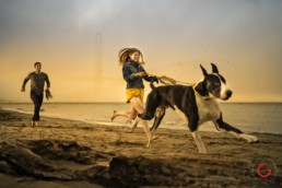 Couple Runs on Beach with Dog in San Fransisco - Photographer Lifestyle Photography Wardrobe Stylist