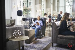 Man enjoys text in a trendy hotel lobby - Professional Photographer Lifestyle Photography Wardrobe Stylist