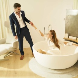 A romantic couple has a playful moment in the bathroom of a hotel room - Professional Photographer Lifestyle Photography Wardrobe Stylist