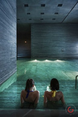 Two ladies enjoy the warm water of the Peter Zumthor Therme at 7132 Hotel in Vals - Professional Photographer Lifestyle Photography Wardrobe Stylist