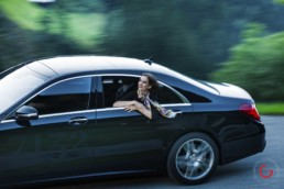 Woman enjoys the view from her limo while driving in the mountains - Photographer Lifestyle Photography Wardrobe Stylist