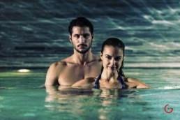 Romantic couple in the warm water of the Peter Zumthor Therme at 7132 Hotel in Vals - Professional Photographer Lifestyle Photography Wardrobe Stylist