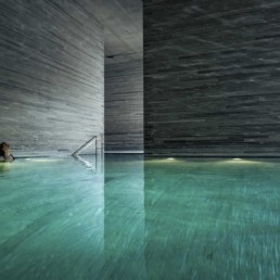 Woman has a Moment of Solace in the 7132 Hotel Therme by Peter Zumthor - Professional Photographer Lifestyle Photography Wardrobe Stylist