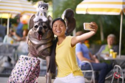 Girl shoots selfie with dog statue and stuffed animal - Professional Photographer Lifestyle Photography Wardrobe Stylist