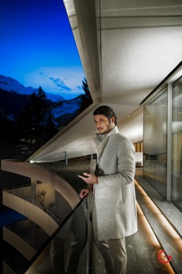 Stylish man takes in evening view of Swiss alps from balcony - Photographer Lifestyle Photography Wardrobe Stylist