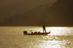 A man fishing boat in Table Rock Lake in the morning mist. Golden sunlight glistens on the water. - Advertising photographers in Branson Missouri, Branson Missouri photography