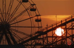 An orange sunset silhouettes the Ferris wheel and roller coaster at celebration city. - Advertising photographers in branson Missouri, Branson Missouri photography