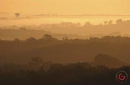 Ozark mountain hills in the morning fog. Golden sun illuminates the cut paper hills. - Advertising photographers in Branson Missouri, Branson Missouri photography