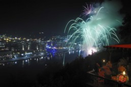 Diners gather on a balcony overlooking the Branson Landing to enjoy fireworks over lake Tanycomo. - Advertising photographers in Branson Missouri, Branson Missouri photography