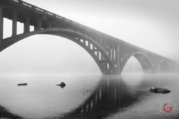 Early morning fog casts the downtown Branson bridge in dim ghostly light while the water on lake Tanycomo reflects like a mirror. - Advertising photographers in Branson Missouri, Branson Missouri photography