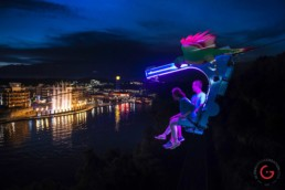Couple rides the zip line at the Branson Landing at night while the fountain show plays in the background - Advertising photographers in Branson Missouri, Branson Missouri photography