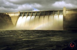 Table Rock Dam with all of the flood gates open in the morning. A rainbow hangs in the mist.