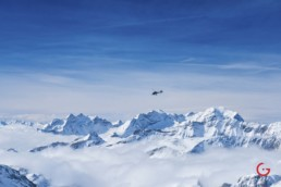 A Private Helicopter Hovers Over The Snow Covered Swiss Alps - Travel Photographer and Switzerland Photography